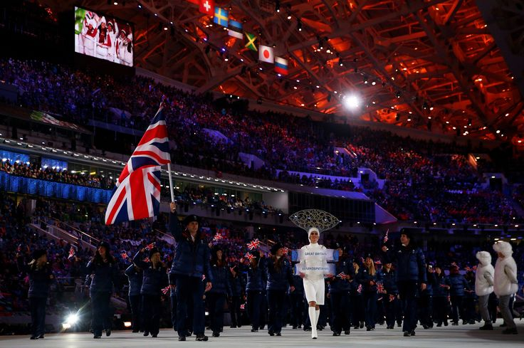 Short track speed skater Jon Eley of the Great Britain Olympic team carries his country's flag during the Opening Ceremony of the Sochi 2014 Winter Olympics