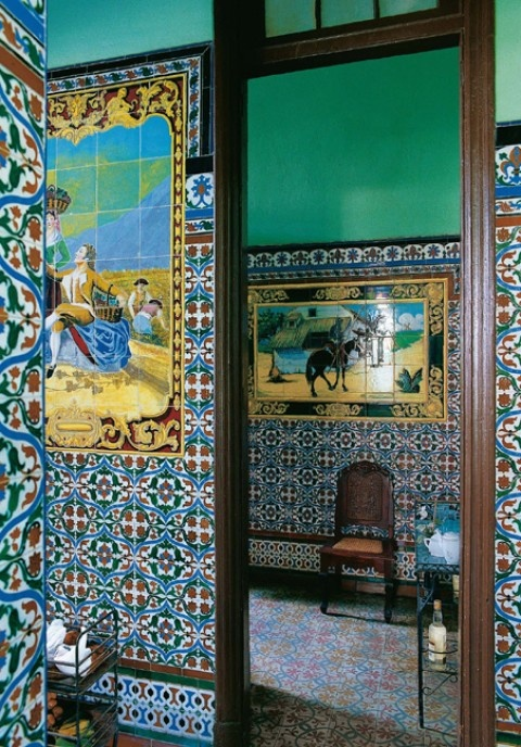"""Jair Mon Pérez House in Havana: The sober tiled walls of the kitchen contrast with the colourful mosaic of Goya's 1792 work """"Muchachos trepando a un árbol"""", visible in the background. From """"Inside Cuba"""""""