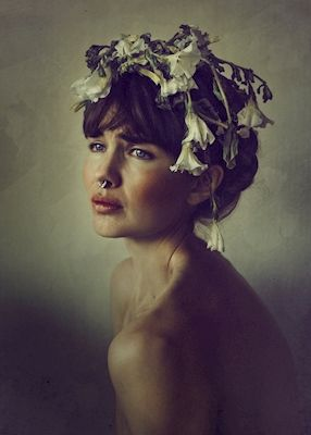 Beautiful photograph with a vintage look to it, of a woman with flowers in her hair and nose piercing. Photograph by LisaLove Bäckman. Available as poster at printler.com, the marketplace for photo art.