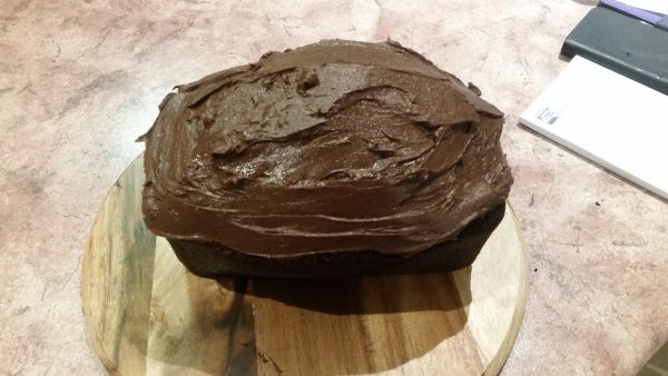 Image Description: a picture of Devil's Food Cake iced and ready to eat on a round wooden chopping board