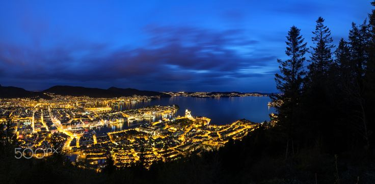 The city of Bergen by Night - Long exposure shot of Bergen, Norway at night, with clouds streaking across the sky, and nice reflections in the water from the city lights.