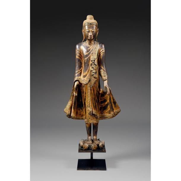 GRANDE STATUE DE BOUDDHA en bois laqué, doré et applications de verroterie, représenté en pied sur un socle lotiforme, les yeux mi-clos, les cheveux coiffés en boucles recouvrant l'ushnisha, les bras tendus le long du corps, retenant les pans de son vêtement liturgique, le fruit du myrobolan dans la main droite. Birmanie, Mandalay, XIXesiècle. Un socle en métal. A VERY LARGE GILT AND BLACK LACQUERED WOOD FIGURE, BURMA, MANDALAY STYLE, 19THCENTURY. HAUT. 160cm (63 IN.)