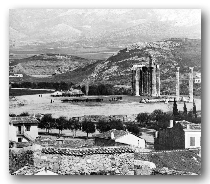 Ασκήσεις τμημάτων του ελληνικού στρατού στους Στύλους του Ολυμπίου Διός. Δημήτρης Κωνσταντίνου, περ. 1870, Αθήνα.  Στη φωτογραφία μας, ακριβώς πίσω από τον λόφο της Άγρας, απλώνεται ο χώρος , που μετά από 54 χρόνια θα φιλοξενείσει του μικρασιάτες πρόσφυγες, ο Βύρωνάς μας. Στο πρώτο λοφάκι, αριστερά πάνω από τον λόφο της Άγρας, παρατηρούμε τη Μονή της Αναλήψεως ( πολύ αχνά).