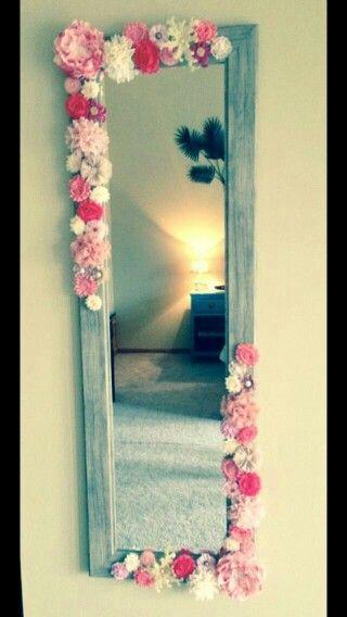 Un espejo con flores rosas y blancas