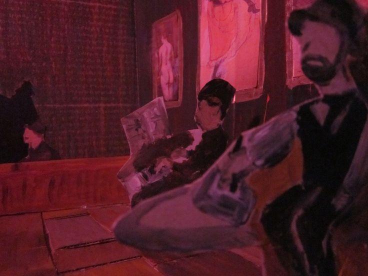 Eindresultaat diorama foto: Toulouse Lautrec op de voorgrond, dame die piano speelt op de achtergrond en deel van de bar. Kunstwerken van Toulouse-Lautrec aan de muur. Getrokken met wit licht met rood crêpepapier voor.