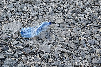 Plastic bottle on pile of rocks and pebbles