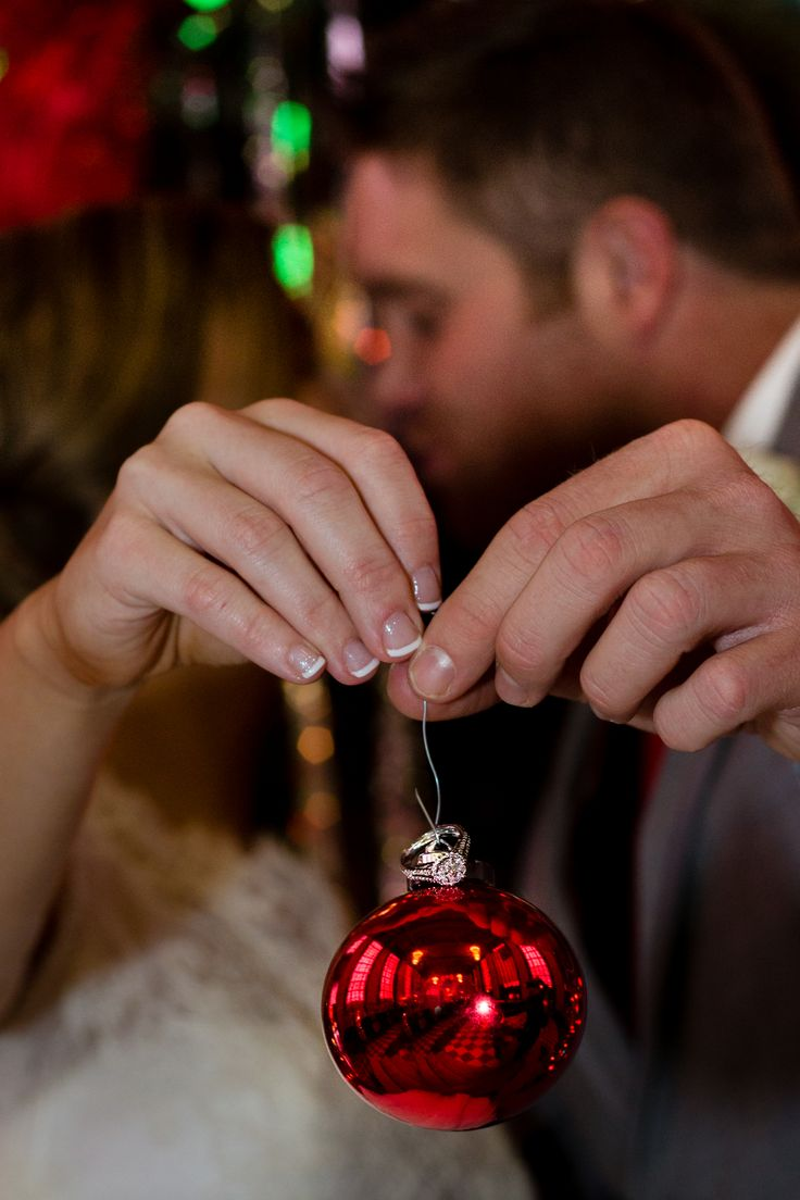 Put the wedding rings in a clear ornament and take a photo of it on the tree or holding it like this!