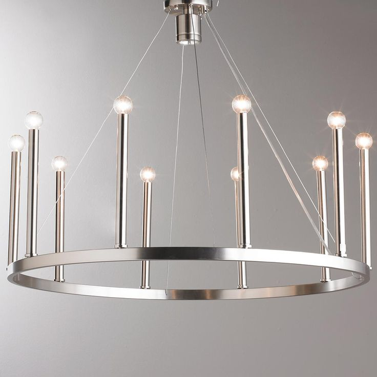 "Euro-Modern Candelabra Chandelier Clean lines and soft curves add to the simplicity of this simple modern chandelier. A halogen bulb fits up in the canopy to shine down the center of the circle and adds to the sharp style this chandelier has to offer. Choose from Bronze or Brushed Nickel. 10x60 watt candle base lamps max and one 50 watt GU10 Halogen lamp max. (25""-52""Hx32""W)"
