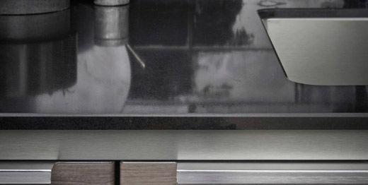 Nærbilde av ei spesialtilpasset benkeplate i kvarts med stålmønstret kant.