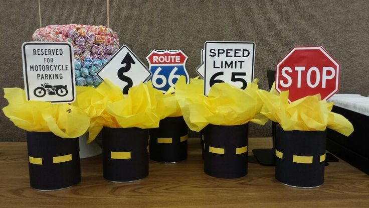 Motorcycle themed centerpieces. Print outs glued to sticks stuck in wrapped cans with tissue paper.