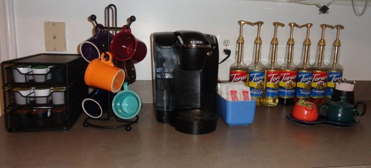 Counter laden with great Coffee supplies. Keurig Brewer, Torani Syrup, K Cup container