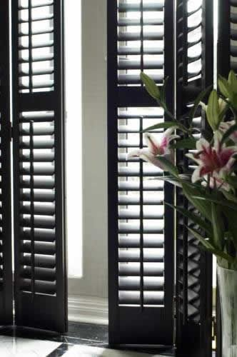 Black modern shutters instead of a curtain. I'm so happy I never found the perfect curtain because this is the answer to that wierd window. Charming and simple. Yes.