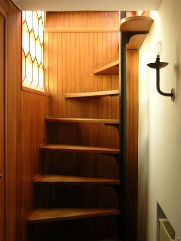 Space saving stairs. This has a lot of the visual and space saving appeal of a spiral staircase without needing to dominate a room.