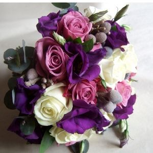 A pretty purple bridesmaid wedding bouquets of ivory Avalanche roses, dusky pink Coolwater roses, deep purple lisianthus , silvery grey brunia berries and silvery green eucalyptus.