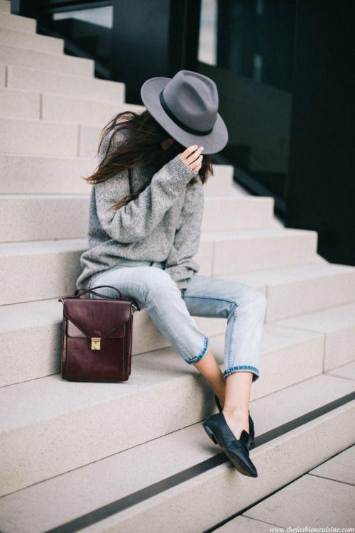 Chic et simple. Jean et pull gris loose, chaussures de lutin en cuir, chapeau et baise en ville.