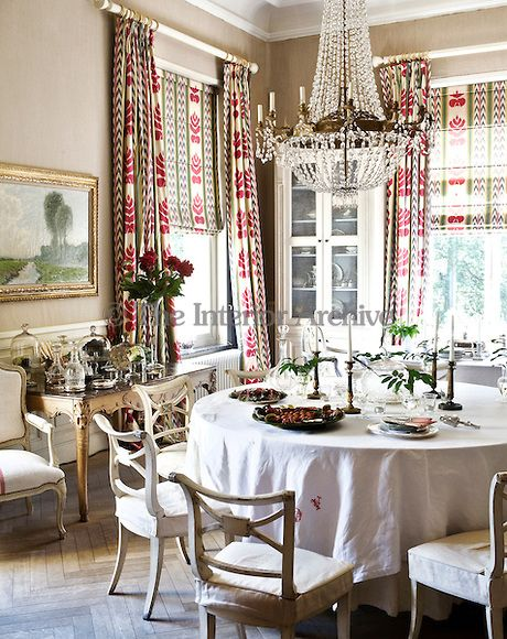 Colourful, patterned curtains adorn the windows of this elegant dining room