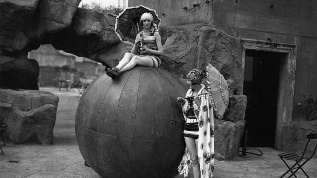 Circa 1928: Two women modeling new beach wear beside a giant beach ball on the roof of an Oxford Street store, London.