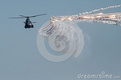 Military helicopter at air show launching rockets.