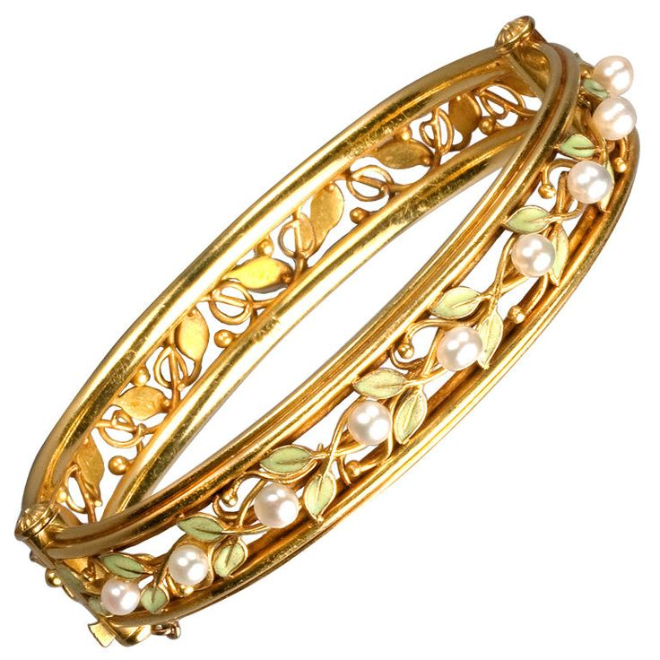 Designed as an openwork vine of high-karat gold and green enameled leaves, the upper half enhanced with fresh water pearls. The gold bracelet opens on a hinge and is fitted with a plunger clasp. A masterpiece of American Arts and Crafts jewelry, circa 1910