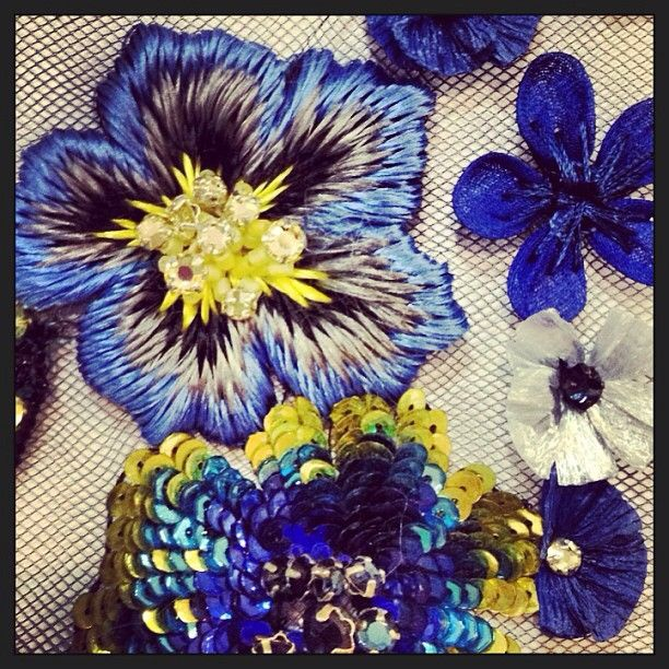 """Hand embroidered pansies in deep blues and golden yellows using sequins and beading, created in Matthew Williamson's design studio. """"Up close and personal with our hand-worked pansies. A red carpet moment in the making? #LFW #BehindTheSeams #CatwalkCountdown"""""""