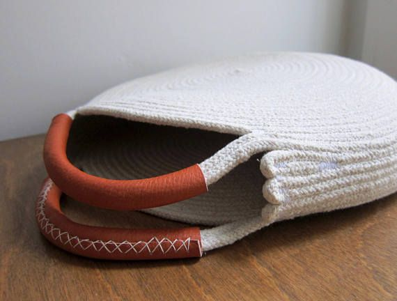 Round purse made out of coiled cotton rope with leather-wrapped handles. Pair it with your summer dresses and add a tassel or silk scarf as a personal touch. This bag is durable and roomy enough to fit all your necessities - measures about 12 inches across and 2 inches deep, with about 3 inch handles. The cotton rope has polyester threads hidden in the center to prevent stretching and to make it lighter. The rope is sewn into the spiral on my sewing machine and the final assembly is finished…