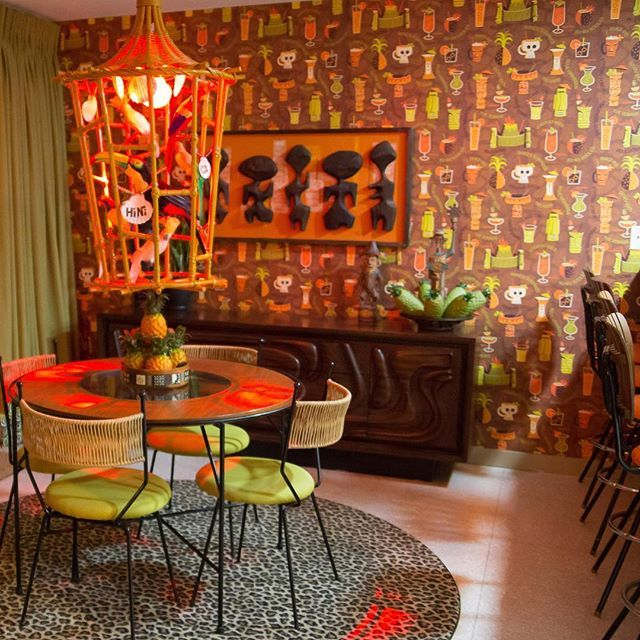 """Palm Springs, my pad. Art by @tikibosko. Birdcage lamp and wall paper by me. Table and chairs by Arthur Umanoff. """"Witco Oceanic"""" credenza by Lane. I'm gonna abandon art to become an interior decorator. Who wants to be my first client? #palmspringspad #tikicaliente #arthurumanoff #witcooceanic.."""