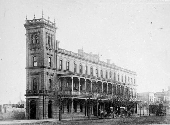 Bendigo, Victoria, 1890. The City Family Hotel. J. Crowley 's Livery and Letting Stables are on the left There are three horse-drawn vehicles in the street. The hotel is three storeys with a verandah along the ground level and a balcony on the first floor.