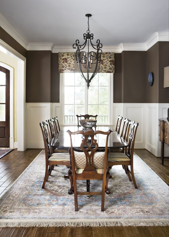 This custom dining room creates a cozy dinner retreat with deep chocolate walls that reflect the warm hardwoods below. Wainscoting and crown moldings lighten the space and reflect light let in by a large front window. Milestone Custom Homes | Greenville SC