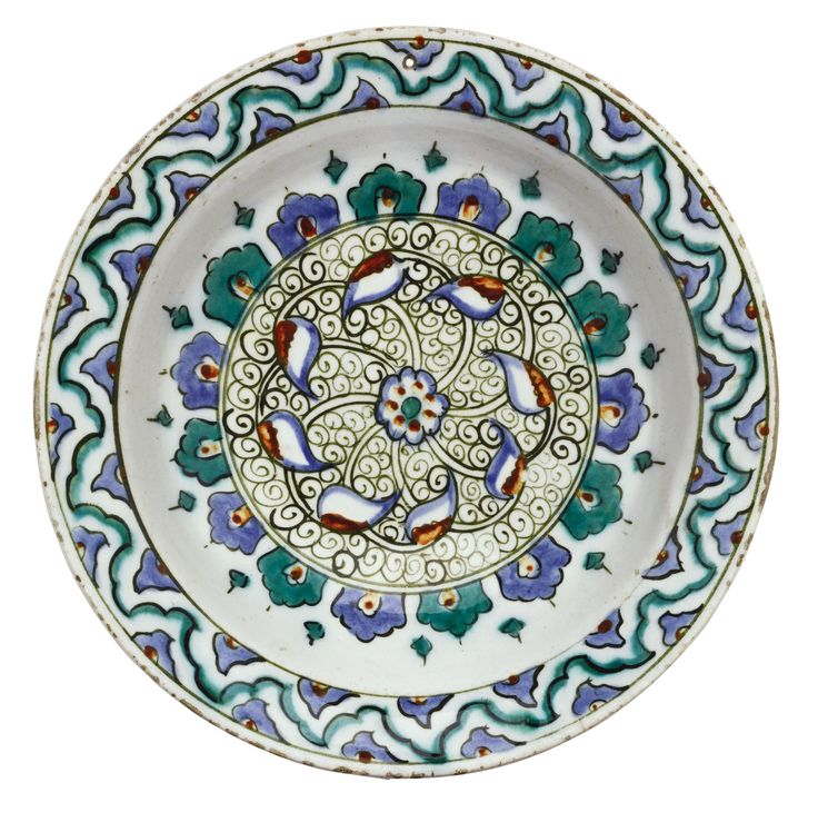 AN IZNIK POLYCHROME POTTERY DISH, TURKEY, CIRCA 1585-90 of shallow round form with an everted rim, decorated in underglaze cobalt blue, viridian green and relief red, the centre with a rosette and overlapping leaves against a pattern of small tight spirals, bordered by arched panels, the rim with a colourful abstract design, floral motifs to exterior 30.3cm. diam.