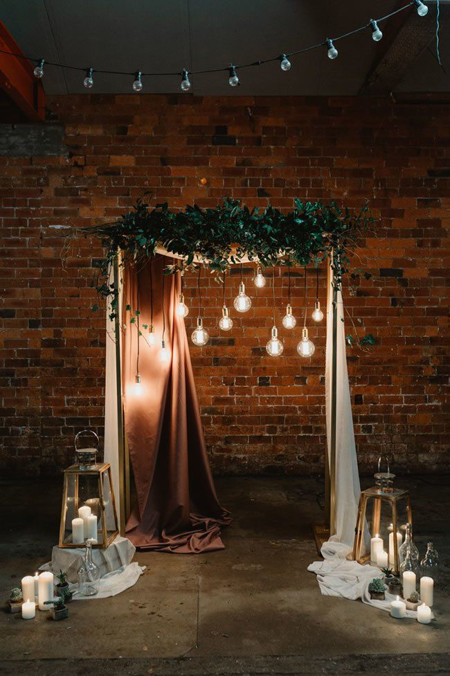 A moody industrial wedding ceremony structure with greenery and hanging globe lights. Here are 6 Ideas for your Industrial Wedding Arch from Here Comes The Guide! #industrialchic #industrialwedding