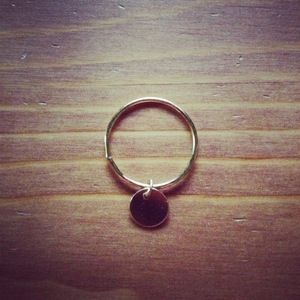 This gold filled ring is size 5. It has a solid circle charm attached that moves freely around the ring. enjoy :)
