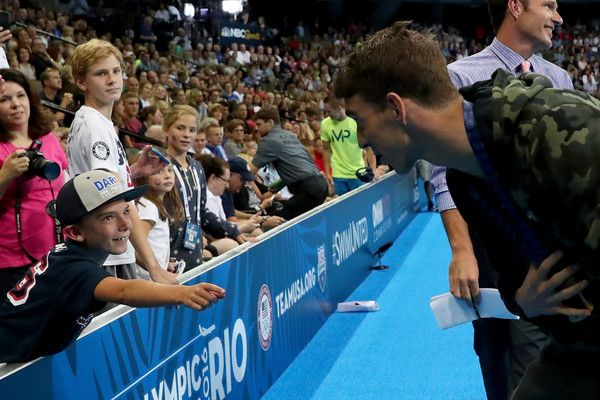 Michael Phelps Photos Photos - Michael Phelps of the United States talks to a young fan after participating in the medal ceremony for the Men's 100 Meter Butterfly during Day Seven of the 2016 U.S. Olympic Team Swimming Trials at CenturyLink Center on July 2, 2016 in Omaha, Nebraska. - 2016 U.S. Olympic Team Swimming Trials - Day 7