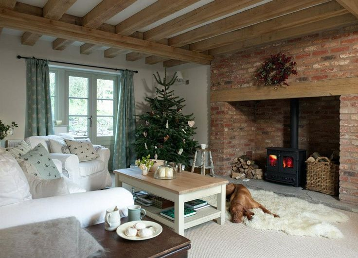 A simply decorated tree and a few accent candles ring in the holidays | 35 Cozy Living Room Ideas with Fireplaces • Unique Interior Styles