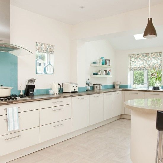 The bright blue glass splashback breaks up the white expanse of this kitchen, giving it a fun touch. The graphic blinds and tonal accessories give the look a continuous feel.