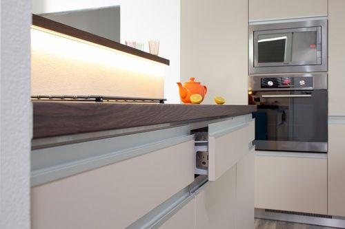 Když se řekne zásuvka, tak si polovina lidí představí elektrickou zásuvku a proto se zásuvky v kuchyni nazývají výsuvy. Ať to nazveme jakkoli, jedna věc je jasná, jedná se o prvek každé praktické kuchyně. Jakmile výsuvy navrhne i zkušený designer kuchyní, mají z toho dokonalý užitek i uživatelé. Horizontální linie zásuvek je podtržena použitými eloxovanými profily. Je to řešení, které kuchyňský ostrůvek opticky prodlužuje a spolu s kovovým soklem působí elegantně. Kovový povrch je doplněn…