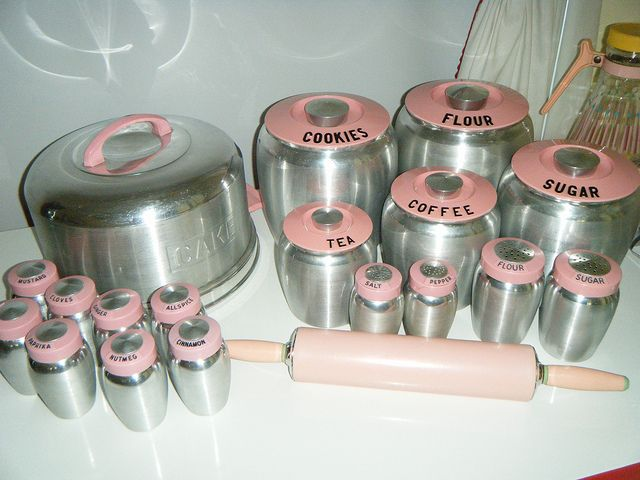 Kromex pink handled cake carrier, canister sets, shakers, spice jars, and rolling pin.