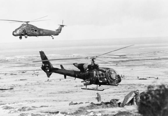A Wessex 5 and a Gazelle helicopter manoeuvre in close proximity above Goat Ridge while 2nd Battalion Scots Guards dig in during the advance towards Port Stanley. © Crown copyright. IWM (FKD 320)