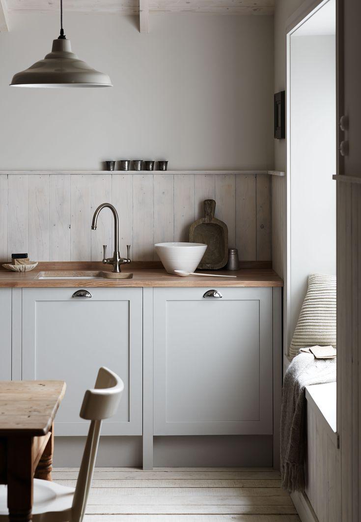 Reforma de cocina rural sencilla y armoniosa. Frentes gris claro, encimera de madera, suelo y techos de madera en blanco.
