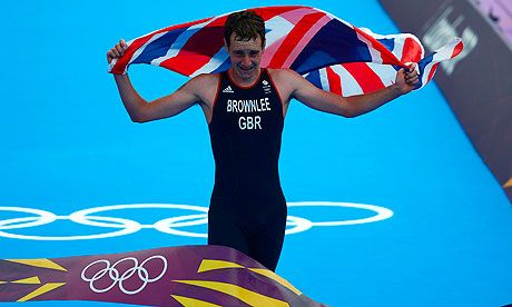 Britain's Alistair Brownlee celebrates with the Union flag while crossing the finish line to win the men's triathlon. Jonny Brownlee, Alistair's 22-year old brother, finished in third place to take bronze.