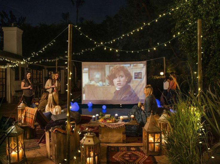 soirée cinéma en plein air - écran de projection, lanternes, tapis à motifs et guirlandes lumineuses