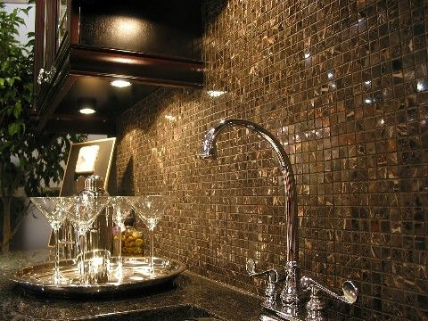 All that glitters...also protects your kitchen.........Small stone tiles with color variation add a glamorous look without being showy. At least until you get close enough to see all the colors clearly.