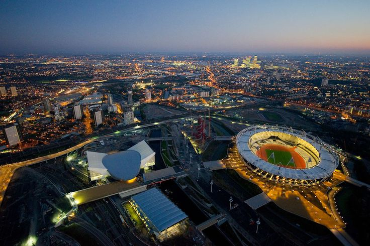Dusk aerial view over the London 2012 Olympic Park, showing the London Aquatics Centre (center left), Water Polo Arena (bottom center), and Olympic Stadium (right)