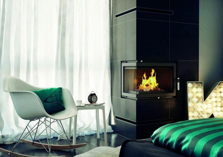 insert cheminée d'angle encastrée dans un coffrage repeint en noir, chaise à bascule Eames et rideaux blancs