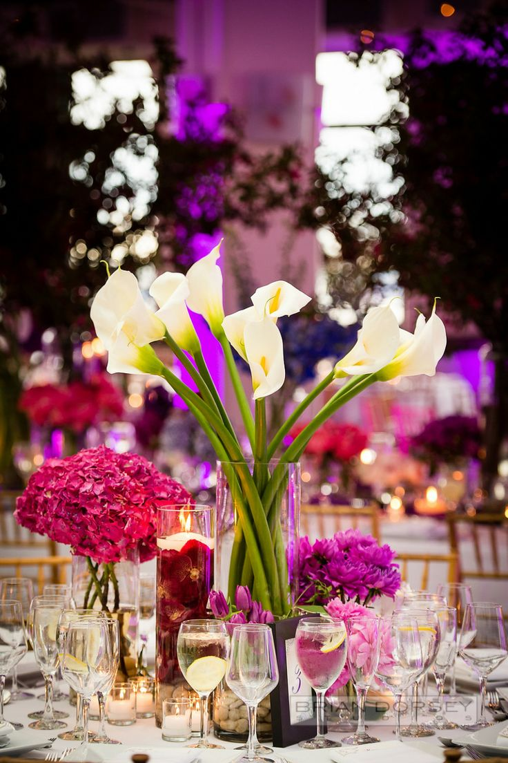 Colorful Wedding Flowers - Tall White Calla Lilies   See the spectacular setting on #SMP here: http://www.StyleMePretty.com/tri-state-weddings/2014/04/18/colorful-indian-wedding-at-tribeca-rooftop/ Photography: BrianDorseyStudios.com   Floral Design: VillanuevaDesigns.com