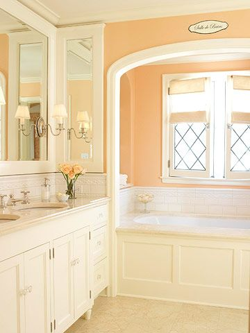 Softly Elegant - An almost-orange shade of coral is a chic update for a white bath. Decorative tile lines the tub and vanity. Lattice window mullions and white trim enhance the traditional look. Small silver sconces mounted on the mirror give this room effortless elegance.