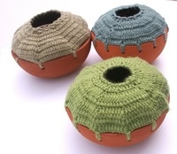 Pots with blue, grey and green crocheted tops.