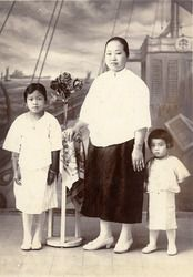 Studioportret van een Chinese vrouw met twee kinderen te Malang