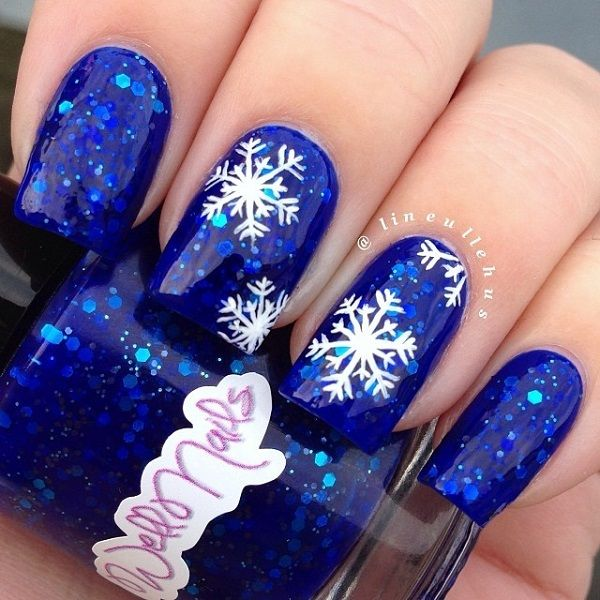 Beautiful blue and white snowflakes nail art design. Painted with sequins in sandwich style nail art, white snowflakes are painted above the nails giving the impression of snow in a sparkling night sky.