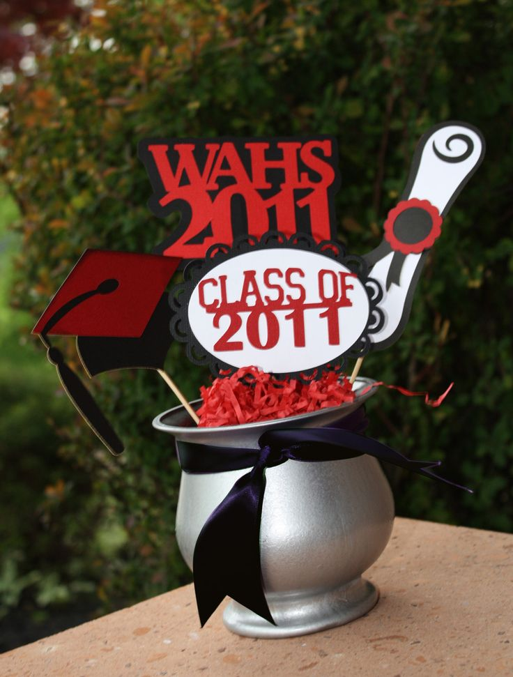 Graduation party centerpiece idea. Spray paint the vase I have with silver or looking-glass paint!  Change the year.  Use Cricut to cut out the decorative stuff on the skewers.  Fill vase with shredded paper in school color.