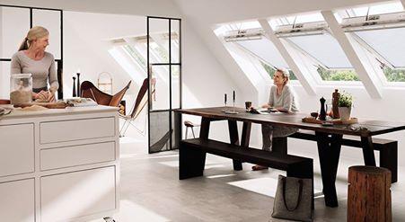 Un grupo de tres ventanas para techo VELUX INTEGRA® inunda de abundante luz natural esta cocina del segundo piso, ofreciendo al mismo tiempo una fantástica vista.